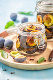 Homemade pickled purple plums in the jar - 220553582