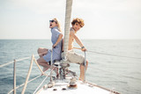 Young european romantic couple smiling at camera while sitting at bow of boat, back to back, enjoying their holidays. Beautiful sea views with copyspace. Hapiness, People Relation, Sea vacation - 220562157