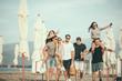 Friends on beach walking, having fun, dancing, couples hugging