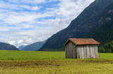 A wooden cabin in the green fields of Tyrol, Austria - 220570383