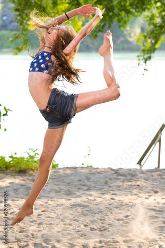 Teenage girl ballet dancer on sandy beach