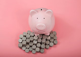 Large pink piggy bank standing on piles of quarters, coins stacked. Saving and investing concept. - 220599308