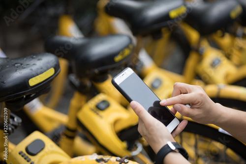 Fototapeta People hands using smartphone scanning the QR code of shared bike in city