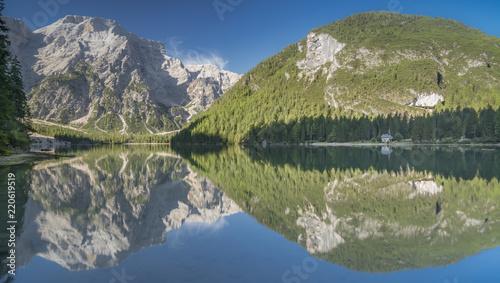 Bergsee am Morgen mit kompletter Spiegelung von Bergen und Kirche - blauer Himmel