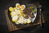 Dillkartoffeln, gekochte Kartoffeln, Dill-Rahm-Sauce, gekochte Eier und Rindfleisch serviert auf einem braunem Teller auf einem schwarzen Holztisch, österreichisches Gericht - 220620185