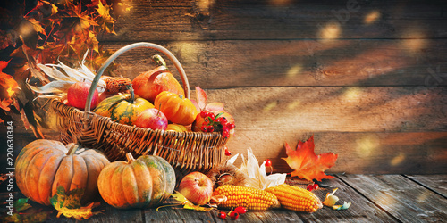 Thanksgiving pumpkins with fruits and falling leaves - 220630384