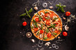 canvas print picture - Tasty pizza with cherries, onions and mushrooms on a black background