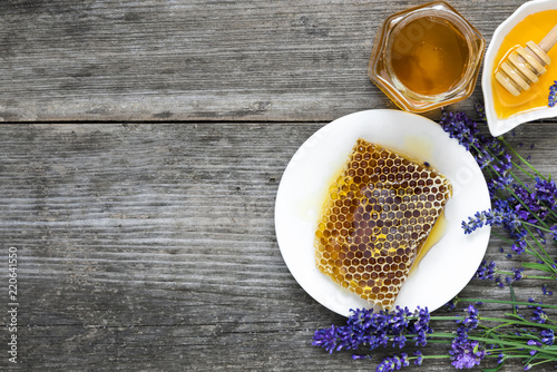Honey with lavender flowers and honeycombs on rustic wooden table. healthy food. top view