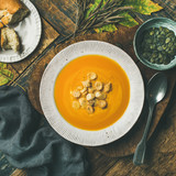 Flat-lay of fall warming pumpkin cream soup with croutons and seeds on board over rustic wooden background, top view, square crop. Autumn vegetarian, vegan, healthy comfort food eating concept