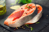 Salmon. Raw trout fish steak with herbs and lemon on black slate background. Cooking, seafood - 220643536