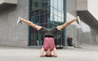 Young man doing yoga headstand exercise outdoors