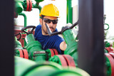 Engineer, working with pipeline controls inside oil and gas refinery - 220652117