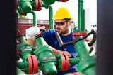 Engineer, working with pipeline controls inside oil and gas refinery - 220652394