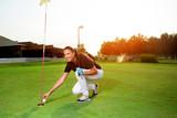 Female golf player with a golf club - 220654941
