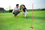 Young couple playing golf - 220655726