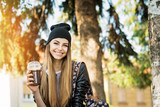 Cheerful teenage female student, drinking coffee in park on sunny autumn day. Closeup, natural lighting, medium retouch. - 220657378