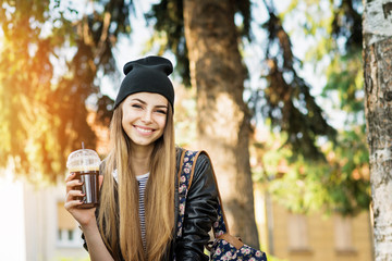 Cheerful teenage female student, drinking coffee in park on sunny autumn day. Closeup, natural lighting, medium retouch.