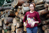 young girl having fun in the forest, posing near the logs - 220670982