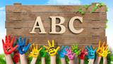 in bunten Farben angemalte Kinderhände und Schild mit Aufschrift