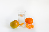 The glass of clean water, apple and citrus on the white background