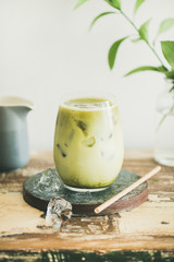 Iced matcha latte drink in glass, white wall and plant branches at background, copy space, close-up, vertical composition. Summer refreshing beverage cold drink