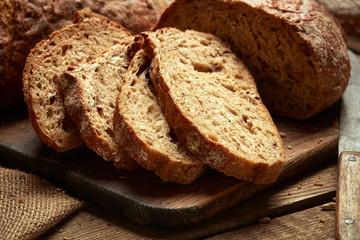 sliced fresh baked bread on wooden background