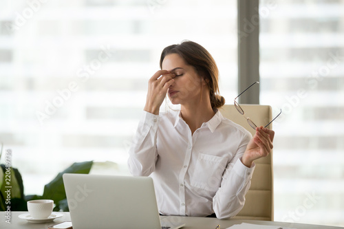 Leinwanddruck Bild Fatigued businesswoman taking off glasses tired of computer work, exhausted employee suffering from blurry vision symptoms after long laptop use, overworked woman feels eye strain tension problem