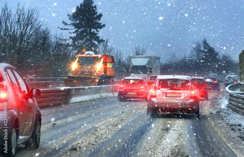 Leinwanddruck Bild Streufahrzeug bei Schneematsch und Straßenglätte auf Autobahn im Berufsverkehr
