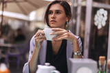 Attractive brunette bussines woman with tail drinking coffee or tea in restaurant. cofee break - 220698708