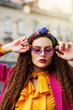 Outdoor close up fashion portrait of young beautiful woman wearing trendy violet sunglasses, colorful headband, circle hoop earrings, yellow blouse, pink blazer, posing in street of european city.