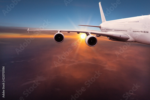 Big commercial airplane flying above dramatic clouds. - 220703186