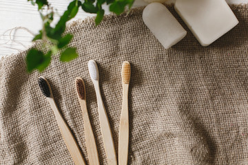 eco natural bamboo toothbrushes on rustic background with greenery. sustainable lifestyle concept. zero waste flat lay. bathroom essentials, plastic free items © sonyachny