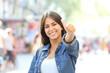 Leinwandbild Motiv Happy girl posing with thumb up in the street