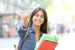 Leinwanddruck Bild - Happy student posing with thumbs up in the street