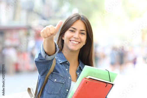Leinwanddruck Bild Happy student posing with thumbs up in the street