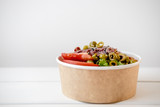Take away salad in disposable craft paper bowl on white background. Minimalism food photography concept. Mockup, copyspace - 220714556