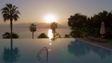 Outdoor swimming pool with deck-chairs and trees around. Resort scene with sea and sun going down behind the mountains - 220715396