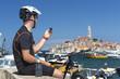 Leinwanddruck Bild - Kroatien, Istrien, Rovinj, Hafen, Mountainbiker bei Pause blickt auf sein GPS-Gerät