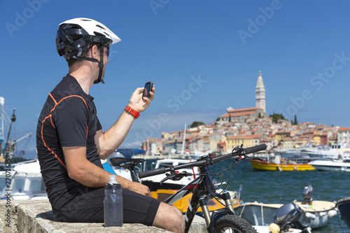 Leinwanddruck Bild Kroatien, Istrien, Rovinj, Hafen, Mountainbiker bei Pause blickt auf sein GPS-Gerät