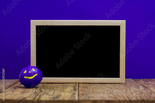 Halloween background concept. Blackboard with decor pumpkin on wooden table and purple backdrop - 220723187
