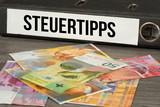 Ein Ordner mit dem Aufdruck Steuertipps und Banknoten Schweizer Franken