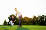 Couple playing golf together on golf course - 220747518