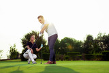 Couple playing golf together on golf course - 220747535