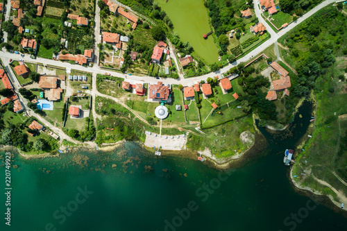 Aerial view of small village on a lake coast with calm clear water