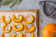Baked pumpkin slices with thyme on a wooden board over grey table. Seasonal food vegetarian recipe. Top view, flat lay.