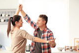 Lovely couple dancing together in kitchen - 220752116