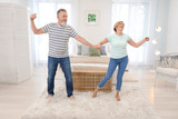 Happy mature couple dancing at home - 220752178