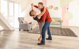 Happy mature couple dancing at home - 220752179