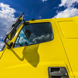 Yellow truck on blue sky background - 220763965