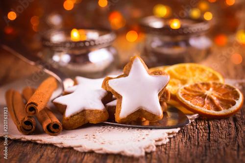 Duftende Zimtsterne und Gewürze auf dem gedeckten Tisch zu Weihnachten - 220763923